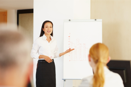 Portrait of pretty young Asian female executive smiling while presenting at office